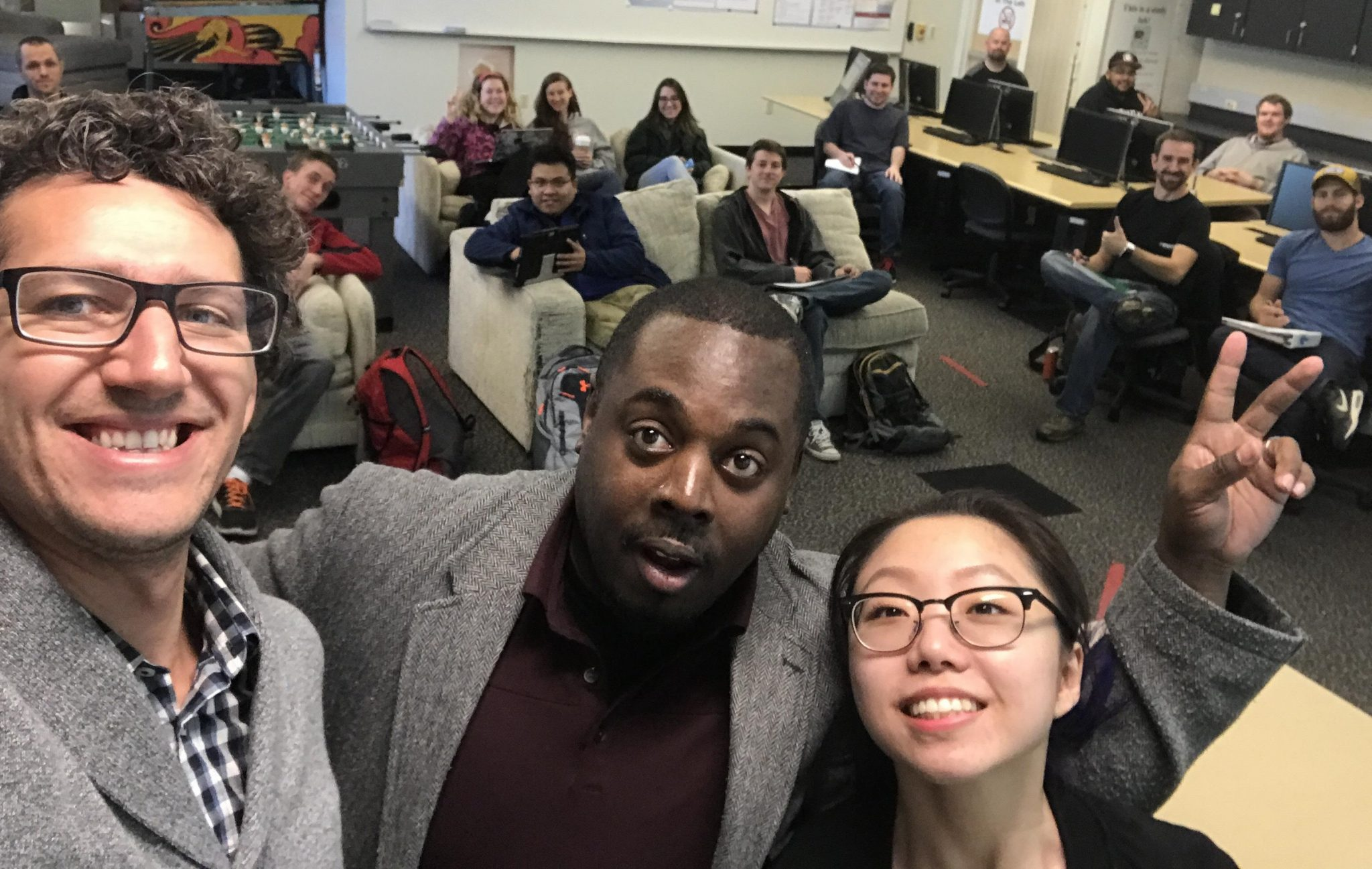 Selfie containing three presenters and thirteen visible students.