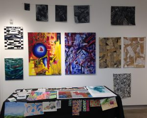 12 paintings on wall, numerous prints on table