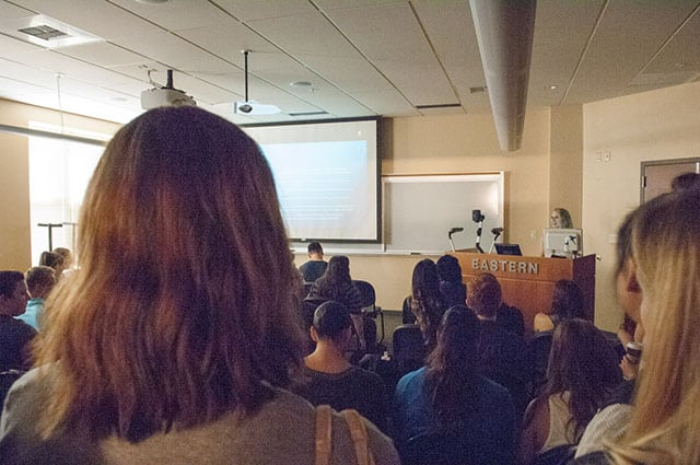 woman speaks at symposium, class full of students