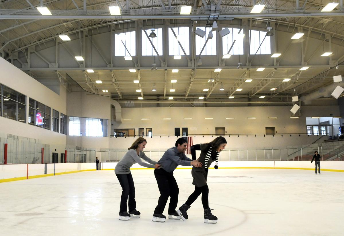 three people skate in train formation on the ice rink
