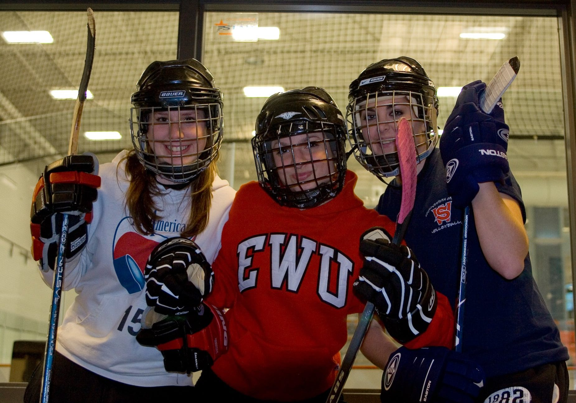Baitlyn, Kayla, and Daitlin pose, wearing hockey gear, in front of the rec center's ice rink