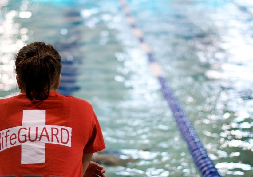 a lifeguard sits next to the pool