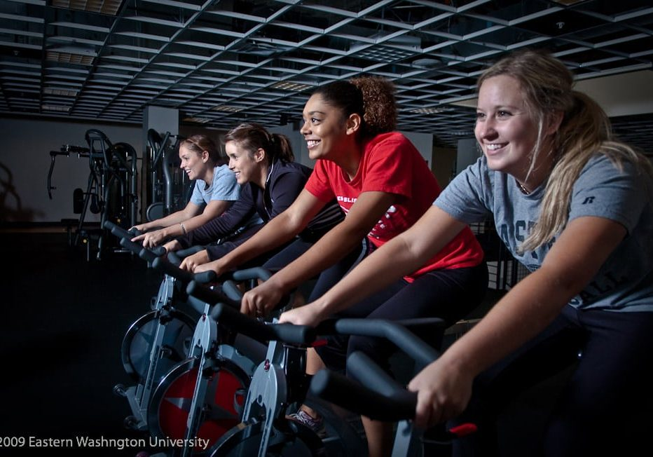 four girls riding the bikes in the URC's gym