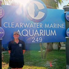 Photo of happy student scholarship recipient in front of the Clearwater Marine Aquarium sign