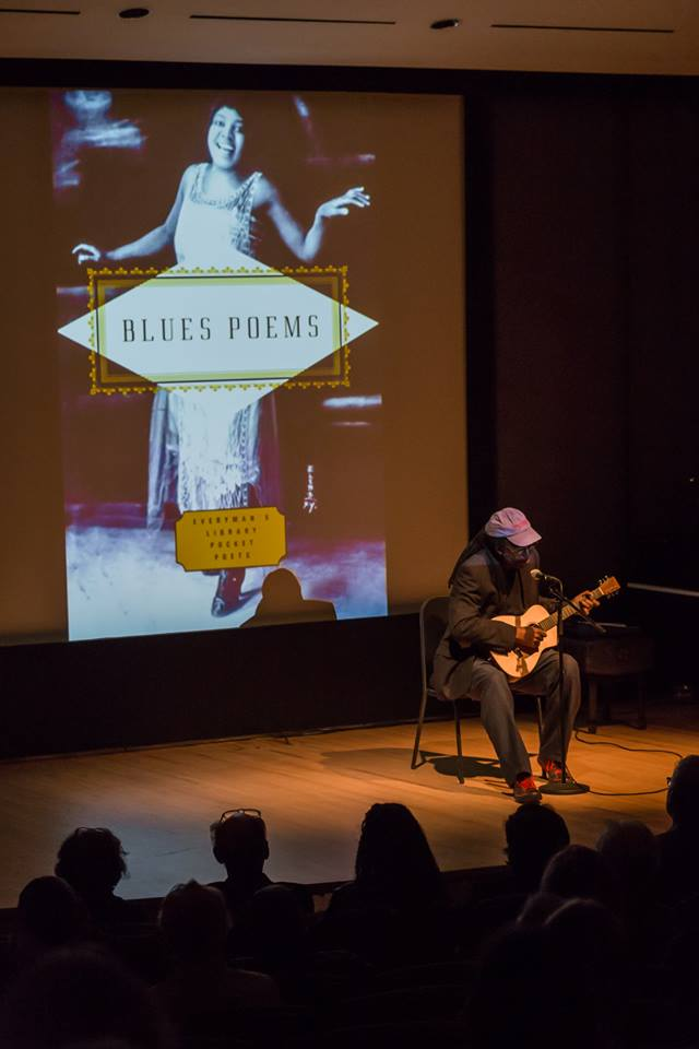 Cornelius Eady performing with a guitar in front of the projected cover of the book called Blues Poems, by Kevin Young