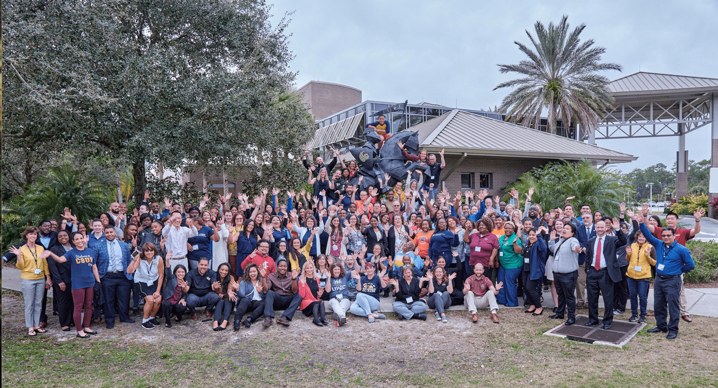 McNair Staff from around the country gather in Florida to talk about best practices - large group photo in front of statue and palm trees