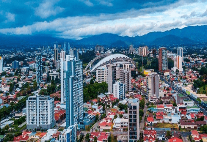 Digital image San Jose Costa Rica, several tall sky scrapers and a stadium, on a blue day with a white streak of clouds
