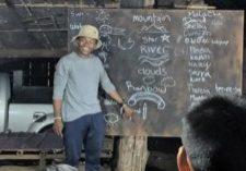 Malachi Chukwu teaches spelling to children in Palong Tribe