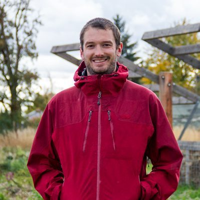 Erik is standing near the campus garden, looking at the camera and smiling with his hands in the pockets of a red zip up jacket.