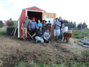 A group of students are pictured beside the red garden shed.
