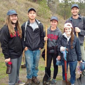 Five office workers are seen holding up shovels and posing for a picture in the woods