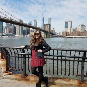Sarah poses in front of a body of water and a landscape of tall buildings