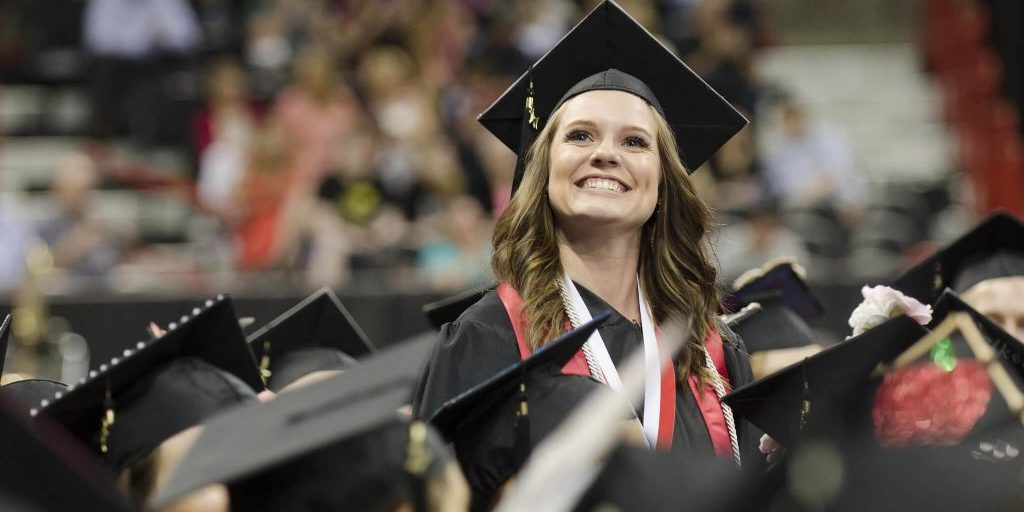 Woman in graduation cap and gown smiling in crowd